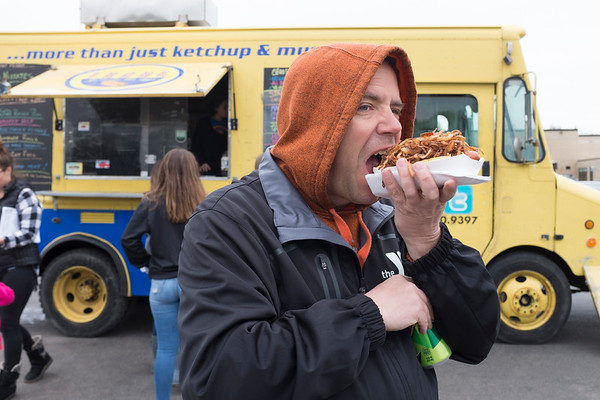 "JOED VIERA/STAFF PHOTOGRAPHER-Lockport,NY- Rick Pytlik takes a bite out of his ""Hogtied"" hotdog from the Frank hotdog food truck."