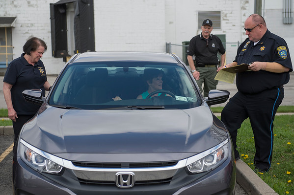 "JOED VIERA/STAFF PHOTOGRAPHER-Lockport, NY- Niagara County traffic of safety office educator Grace Destino, Town of Niagara police officer Mike Rozyczko and Niagara County Sheriffs dispatcher Roger Yurek look over Angie Blackley's vehicle. during the CarFit event at the Dale Association on Wednesday afternoon. Yurek said that drivers are afraid that CarFit technicians are out to take their licenses ""Thats not what we do"" he said. CarFit techs inspect older drivers' vehicles to ensure they are properly adjusted for safety."