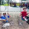 JOED VIERA/STAFF PHOTOGRAPHER-Lockport, NY-   Amillianna Hunt, 7, and Christian Brittain, 7, play on the swings at Day Road Park. The pair are classmates Anna Merritt.