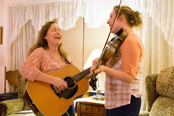 JOED VIERA/STAFF PHOTOGRAPHER-Royalton, NY-Higher Mountain's Christine Kesterson and her daughter Mary Kesterson-Sasso rehearse on guitar and fiddle in the Kesterson's living room.