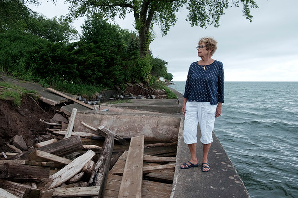 JOED VIERA/STAFF PHOTOGRAPHER-Judy Brounscheidel looks over the remains of her patio along Lake Ontario. Rising Lake levels have claimed close to 20 feet of her property on Lake Side Drive in Somerset.