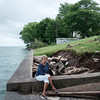 JOED VIERA/STAFF PHOTOGRAPHER-Judy Brounscheidel sits on the remains of her patio along Lake Ontario. Rising Lake levels have claimed close to 20 feet of her property on Lake Side Drive in Somerset.