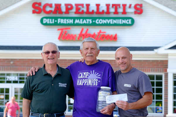 JOED VIERA/STAFF PHOTOGRAPHER-Lockport, NY-Scapelliti's owner's Dominic, left,  and Sam Scapelliti, rght,  hand a check for $600 to  John Zieziula. The funds will help pay for Camp Happiness, a summer day camp for people with intellectual and developmental disabilities. Money was raised by placing a jar by the store's cash register to collect customers unwanted change over a 6 month period starting in January.