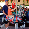 JOED VIERA/STAFF PHOTOGRAPHER-Lockport, NY- Wayne Cameron rides a carousel with his grand sons Garrett, 4, and Cameron Durnford, 7 at the Olcott Beach Carousel Park.