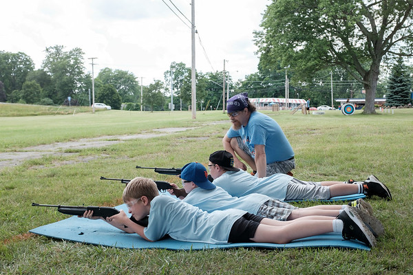 JOED VIERA/STAFF PHOTOGRAPHER-Bryan Dimon looks over den seven Cub Scouts Thomas Tomson, 10, Jackson Pike, 9, and Benjamin Criswell, 10, as they shoot bb guns on a range during the Scouts weeklong day camp.