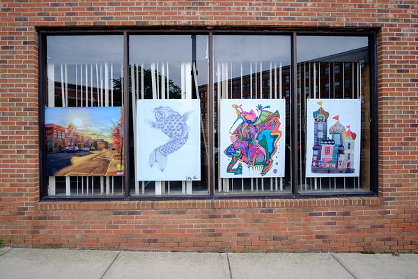 JOED VIERA/STAFF PHOTOGRAPHER-Art hangs on the window of 120 Main Street.