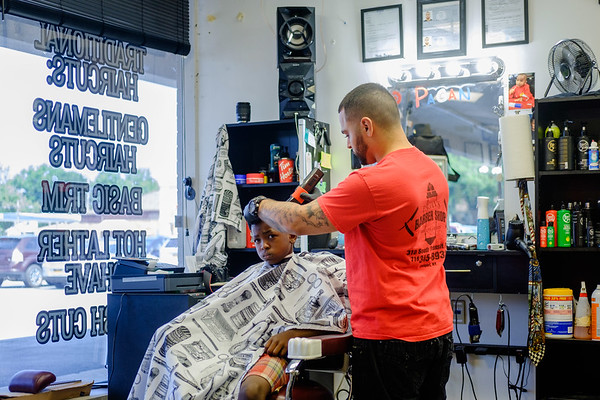 JOED VIERA/STAFF PHOTOGRAPHER-Barber Josh Pagan gives 6-year-old Zion Knight a hair cut. Monday Pagan offered anyone involved woth the city's youth and recreation program free hair cuts.