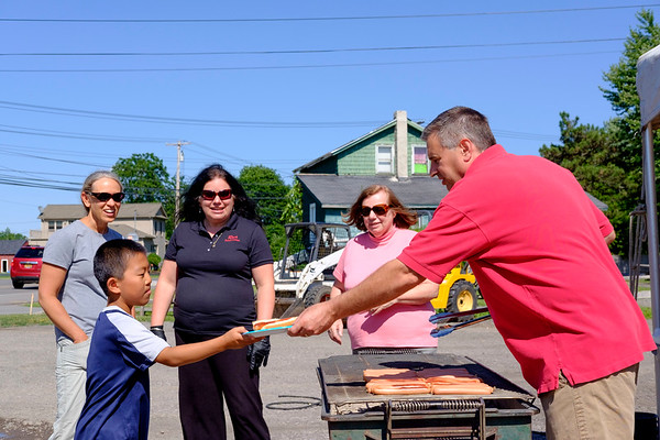 JOED VIERA/STAFF PHOTOGRAPHER-John Ross hands out  a hotdog to Micah Seiler, 8, during Ross Rental's 25th anniversary celebration.