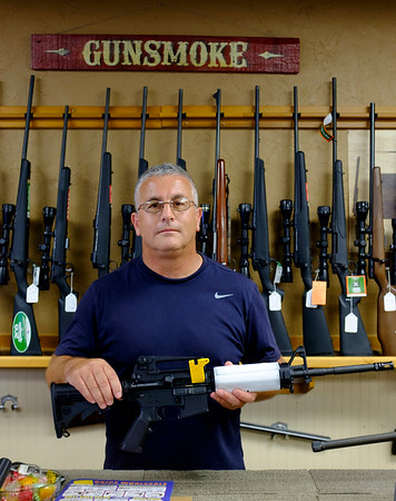 Gunsmoke owner Jeff Hill holds up a Bushmaster AR-15 sporting rifle purchased by a law enforcement officer on Tuesday, August 1st, 2017. The rifle held by Hill has an adjustable stock, a pistol grip and a flash hider, all of which are illegal under the NY State S.A.F.E. act except for law enforcement officers.(Lockport Union-Sun & Journal/Joed Viera)