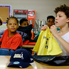 JOED VIERA/STAFF PHOTOGRAPHER-Dalvan Robinson, 13, checks out the swag Peter Suiee, 13, received for perfect attendance in the Game Changers program. While all participants received a t-shirt and a water bottle, those who came every day got a trophy, swag bag and a hat.