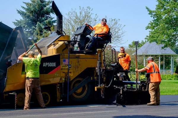 JOED VIERA/STAFF PHOTOGRAPHER-City workers coat Lincoln Drive with blacktop.