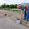 Joed Viera/Staff Photographer-Marina attendant Mike Griesser paints the parking blocks along Nelson Goehle Marina.