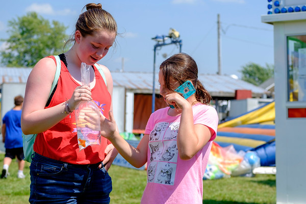 "JOED VIERA/STAFF PHOTOGRAPHER-Rachel Argo, 12, left, calls her mother asking permission to keep a goldfish she won at the Niagara County Fairin Lockport N.Y. on Wednesday, August 2nd, 2017. Argo's mom said no and Elizabeth Kearshaw, 12, right, agreed to give ""Goldilocks"" a new home. (Lockport Union-Sun & Journal/Joed Viera)"