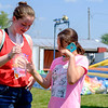 """JOED VIERA/STAFF PHOTOGRAPHER-Rachel Argo, 12, left, calls her mother asking permission to keep a goldfish she won at the Niagara County Fairin Lockport N.Y. on Wednesday, August 2nd, 2017. Argo's mom said no and Elizabeth Kearshaw, 12, right, agreed to give """"Goldilocks"""" a new home. (Lockport Union-Sun & Journal/Joed Viera)"""