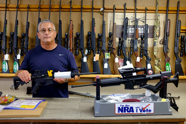 Gunsmoke owner Jeff Hill holds up a Bushmaster AR-15 sporting rifle purchased by a law enforcement officer, comparing it to an ATI Omni AR-15 on the rack on Tuesday, August 1st, 2017. The rifle held by Hill has an adjustable stock, a pistol grip and a flash hider, all of which are illegal under the NY State S.A.F.E. act with an exemption  for law enforcement officers. The ATI Omni on the gun rack excludes all the illegal features. (Lockport Union-Sun & Journal/Joed Viera)