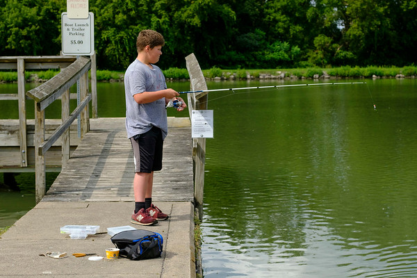 Joed Viera/Staff Photographer-Thursday afternoon, Ryan Winters 11, reels in his rod from the Erie Canal at  Nelson Goehle Marina. Winters had already caught 3 bass using worms as bait and was searching for more.