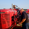 JOED VIERA/STAFF PHOTOGRAPHER-Robert Sharp bangs his bright red Farmall with a wrench attempting to fix it during Cambria's Tractor Pull.