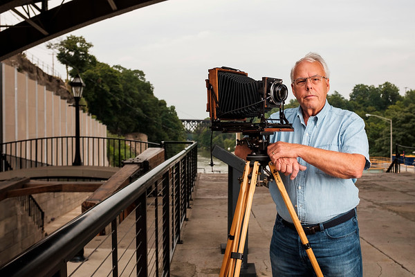 JOED VIERA/STAFF PHOTOGRAPHER-Dennis Stierer poses with his large format 5x7 camera by the flight of five.