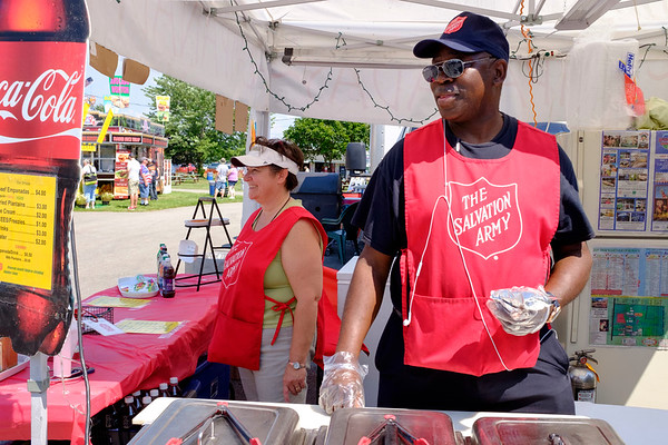 Stefanie Nkounkou looks on as Major Celestin Nkounkou prepares an empanada the Salvation Army's food stand at the Niagara County Fair in Lockport N.Y. on Wednesday, August 2nd, 2017.  (Lockport Union-Sun & Journal/Joed Viera)