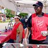Stefanie Nkounkou looks on as Major Celestin Nkounkou prepares an empanada the Salvation Army's food stand at the Niagara County Fair in Lockport N.Y. on Wednesday, August 2nd, 2017.  (Lockport Union-Sun & Journal/Joed Viera)