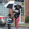 Joed Viera/Staff Photographer-A woman and child cross Main Street  during Wednesday's down pour.