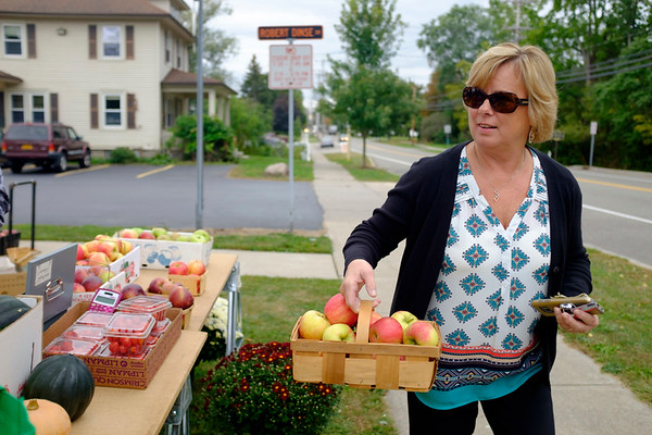 Joed Viera/Staff Photographer- Roxanne Benton buys a buschel of apples at Wilson High School's Farm Stand.