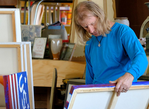 Joed Viera/Staff Photographer- Richard S. Manning picks up one of his 'One Family' paintings. Manning has  painted over 1,800 pieces in memorial of 9/11. Manning has pledged to create 3,000 pieces total.
