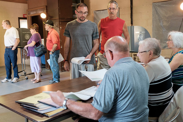 Joed Viera/Staff Photographer-Voters line up as a voting machine malfunctions at the Olcott Park Polling Place during the primary election. Voters were able to leave their ballots to be scanned by the machine later.