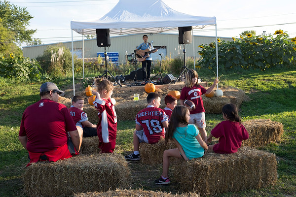Joed Viera/Staff Photographer-Kids play by haystacks as Vincent Bonelli sings at Halmony Farms.