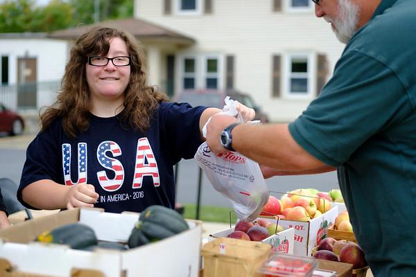 Joed Viera/Staff Photographer- Jenna Gianbra, 17, hands a customer a bag of tomatoes at Wilson High School's Farm Stand.