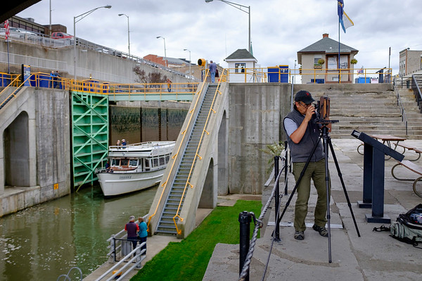 Joed Viera/Staff Photographer-Michael Przybyla adjust settings on his 5x7 film camera before photographing a scene at the Locks. Przybyla was one of seven students participating in a workshop hosted by Tillman Crane and Dennis Stierer. Stierer and Crane have been hosting workshops together since 2011 and chose the Canal as the subject for this years workshop in celebration of the bicentenial of the Erie Canal.