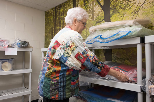 Joed Viera/Staff Photographer-Kathy McIntosh sports a quilted jacket made by fellow guild member Sue McKen as she stacks quilts for the Quilter's Guild's show at the Keenan Center.