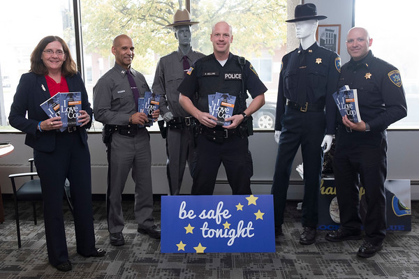 "Joed Viera/Staff Photographer-Mary Brennan-Taylor, NY State Police Zone Commander Eric Laughton,  Lockport Police Officer Aaron Belling and Niagara County Sheriff's Lt. Robert Richards hold up copies of ""I Love A Cop"" dressing up dummys in law enforcement uniforms at the US&J offices for Lockport Blue. Brennan-Taylor and the YWCA donated 200 copies of the book to distrubute to Law Enforcement Officer's families for the month-long event."