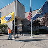 A city worker pulls down the City of Lockport flag Monday afternoon after President Trump ordered all flags to be flown at half-staff for the rest of the week in wake of a deadly shooting in Las Vegas, NV. (Joed Viera/Lockport Union-Sun & Journal)