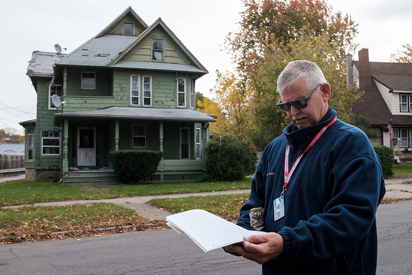 Joed Viera/Staff Photographer-Lockport housing inspector Mark Haenle looks over paperwork in front of 131 Locust Street, a residence the city considers a zombie house.