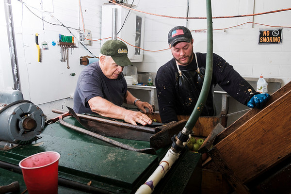 Joed Viera/Staff Photographer-  Lou Hoke and  Nate Hall help apples onto an elevator at Hall's Apple Farm. The pair is working with a wooden apple cider press in use at the farm since 1971.