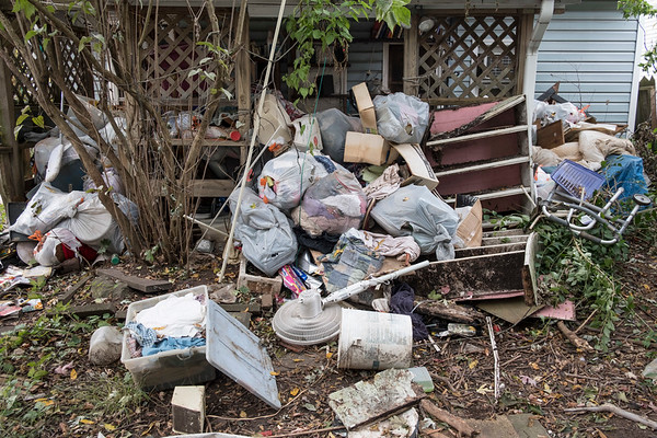 Joed Viera/Staff Photographer-Garbage piled up behind 126 Harvey Avenue, a residence the City considers a zombie house.