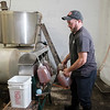 Joed Viera/Staff Photographer- Nate Hall fills jugs with cider at Hall's Apple Farm. The cider is the product from a wooden apple cider press in use at the farm since 1971.