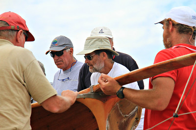 Skipper Ian Smith, center, helping to install the bumpkin.