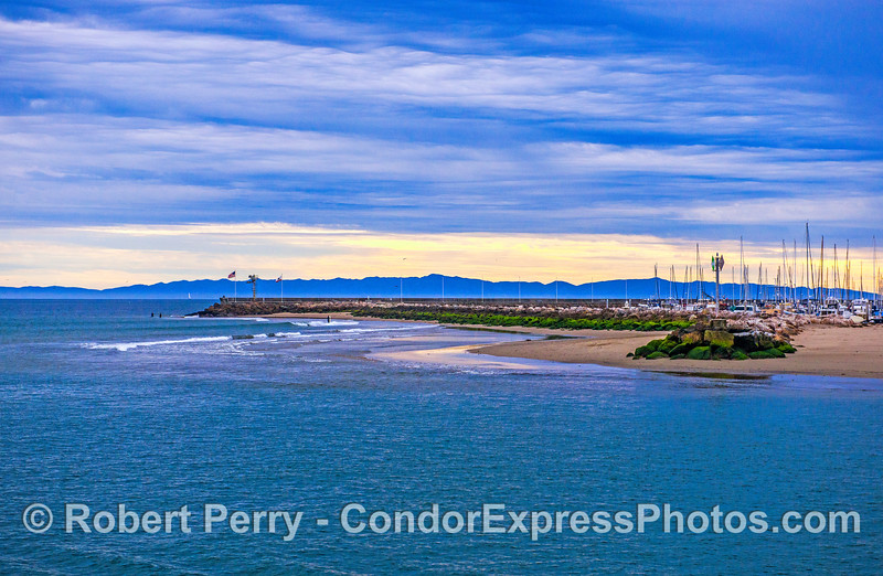 Santa Barbara Harbor entrance showing the Sand Spit and a silhouette of Santa Cruz Island in the background.