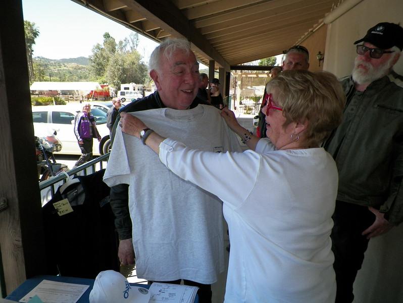 Connie helps John choose a shirt size.