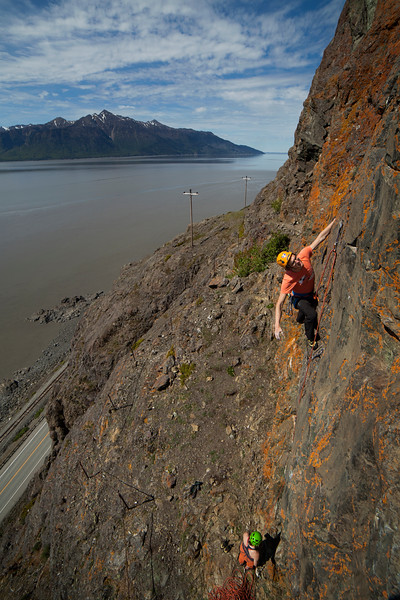 The Turnagain Arm provides the backdrop as Ty works his way up <i>Pocket Rocket 5.10b</i> at Dino Head.