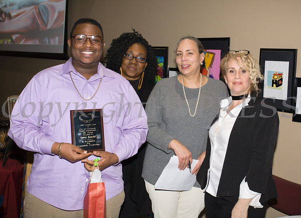 Larry Arnold receives his award from Malinda Ware, Ramona Burton and Rosina Tezgeldi during the City of Newburgh Human Rights Commission sponsored Second Annual Black Pioneers of Newburgh at the Newburgh Free Library on Saturday, February 18, 2017. Hudson Valley Press/CHUCK STEWART, JR.