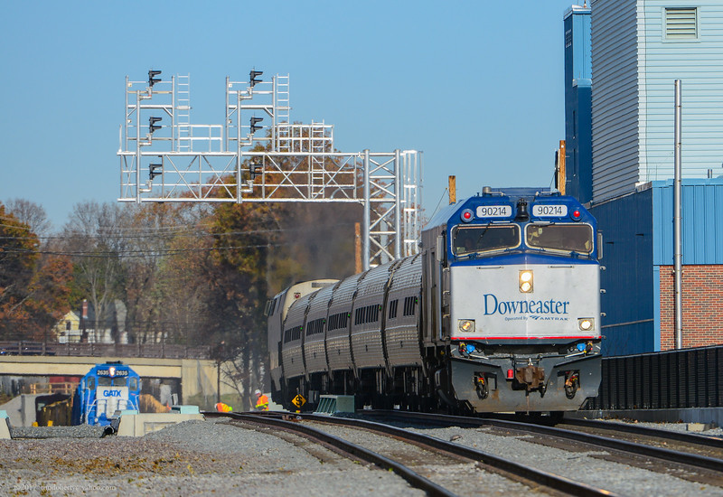 Inbound Downeaster 690 passes through the new Tuffs interlocking in Medford with a ballast train in the backround.