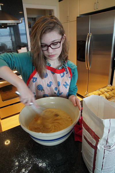 Mara stirs up some pumpkin roll dough.