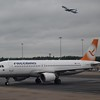 Freebird Airlines orange Airbus A320 TC-FHC taxies at Birmingham as a TUI 757 takes off behind.