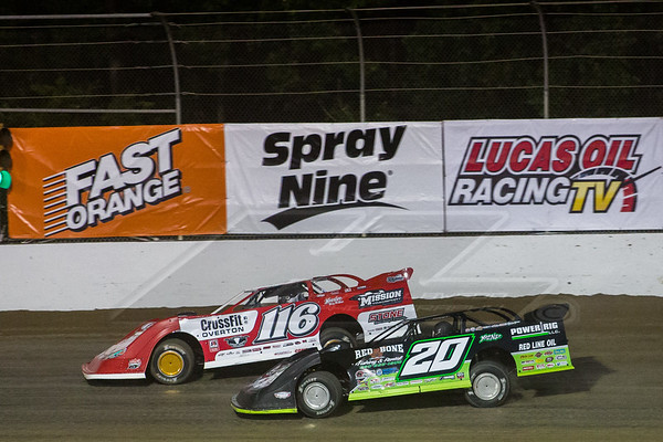 Jimmy Owens (20) and Brandon Overton (116) race under Fast Orange, Spray Nine and Lucas Oil Racing TV catch fence banners