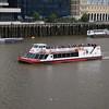 City Cruises tour boat sailing under London Bridge on the Thames.