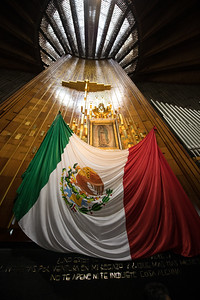 Mexican flag under an icon of Saint Guadalupe.