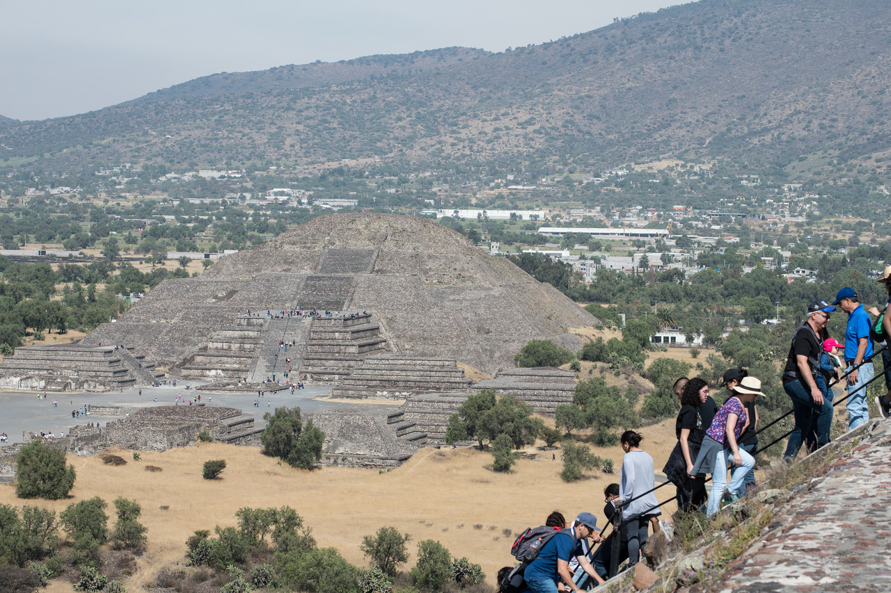 People climbing the Pyramid of the Sun with the  smaller Pyramid of the Moon in the background.